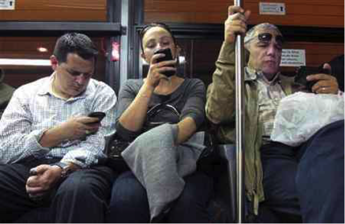 People on their phones on a train