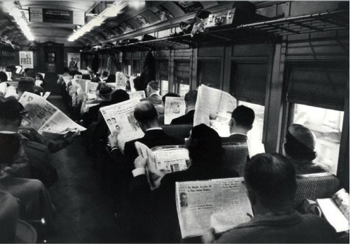 People reading a newspaper on a train